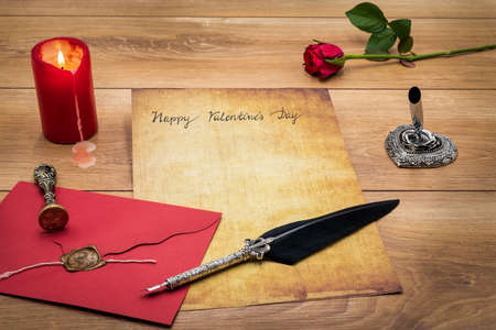 Lovely classic Valentine's Day cad, hand written with ink and quill on vintage paper, red envelope with wax seal, red rose, lit candle, silver quill stand on oak – front view