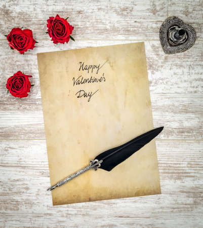 Antique preachment with hand written Happy Valentine's Day, 3 red roses, detailed silver quill stand in shape of hart accented by flat lying beautifully ornamented silver and black quill on rustic white painted oak