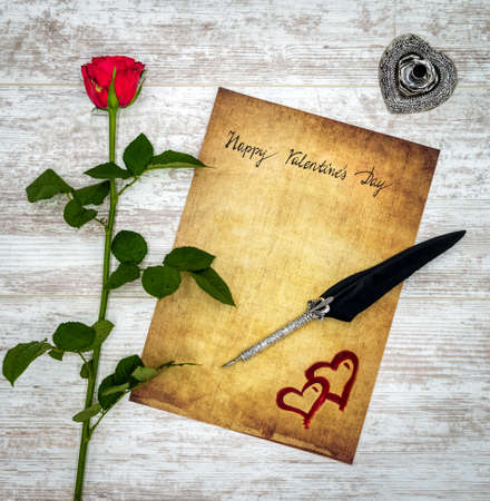 Antique preachment with hand written Happy Valentine's Day, red rose, red painted 2 harts, detailed silver quill stand in shape of hart accented by flat lying beautifully ornamented silver and black quill on rustic white painted oak Stockfoto