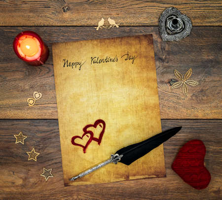 Antique preachment with hand written Happy Valentine's Day, red lit candle, red cuddle heart, red painted hart, wooden decorations, detailed silver quill stand in shape of hart accented by flat lying beautifully ornamented silver and black quill on antique oak