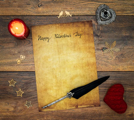 Antique preachment with hand written Happy Valentine's Day, red lit candle, red cuddle heart, wooden decorations, detailed silver quill stand in shape of hart accented by flat lying beautifully ornamented silver and black quill on antique oak Banco de Imagens