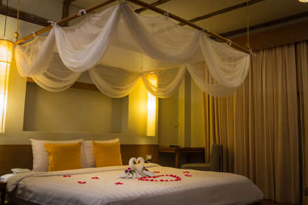 White two towel swans and red rose petals on the bed, Honeymoon decoration