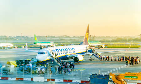 Dublin, Ireland, May 2019 Dublin airport, people boarding airplane, airfield with multiple aircrafts, sunrise and early hour mist