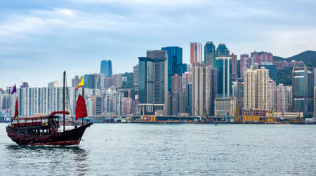 Chinese traditional junk boat in front of Hong Kong skyline