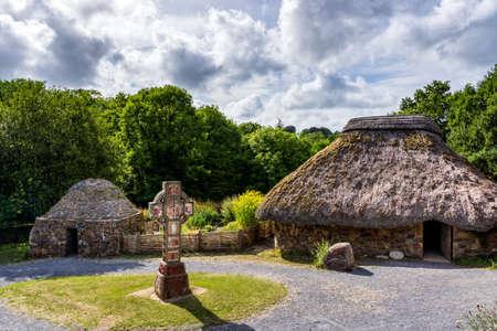 Altes Stroh- und Steinhaus mit keltischem Kreuz in der Mitte, Konzept der frühen menschlichen Siedlung, grüner Wald und stürmischer Himmel im Hintergrund