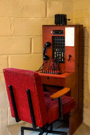 Antique Vintage Telephone Switchboard and red armchair, Communication Connection station Concept
