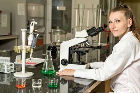 Young, Caucasian white, female laboratory technician in white robe with stethoscope sitting next to compound microscope, laboratory, equipment and glassware in background