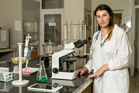 Middle age, Caucasian white, female laboratory technician in white robe with stethoscope standing next to compound microscope, laboratory, equipment and glassware in background