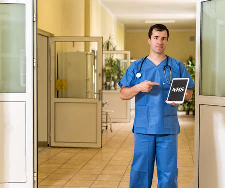 Middle age, Caucasian white, male doctor in blue scrubs with stethoscope holding and pointing to tablet with NHS text, blurred hospital corridor in background 版權商用圖片