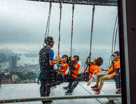 Macau, China, March 2013: Group of people on Sky Walk at Macau Tower in rainy day, popular extreme sport attraction and adrenaline rush activity