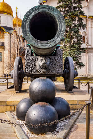 Huge old tarnished ornate canon, Tsar Pushka, on wheels with stack of cannonballs in front, located inside of Kremlin walls, Red Square Moscow Russia