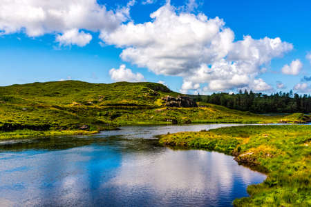 Beautiful shot of a small tranquil pond and river with puffy clouds reflected in water. Scenic green meadows and hills of Connemara, Ireland