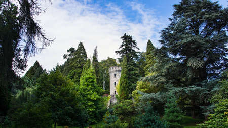 Ruins of ancient guard tower surrounded by green tries in Powerscourt gardens, Wicklow, Ireland