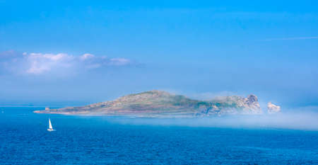 Low lying fog or mist approaching and covering Irelands Eye island, unusual phenomenon, panoramic view from Howth, Dublin, Ireland Stock fotó