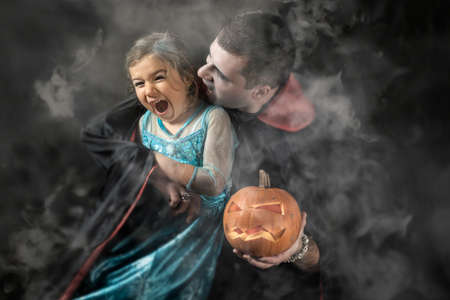 Halloween portrait vampire attacking young princess father and daughter play adult Caucasian white man holding orange pumpkin smoke or fog background Stockfoto