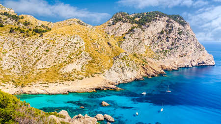 Beautiful coastline view of the cliffs with clear turquoise water and yachts. Cala Figuera beach on Cap de Formentor, Mallorca, Spain