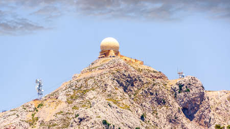 Puig Major observatory on top of a mountain with cloudy blue sky in background, Mallorca island, Spain