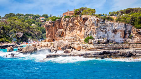 Houses on cliffs around beautiful beach, Cala Llombards in Mallorca, turquoise water and blue sky, Balearic Island, Spain