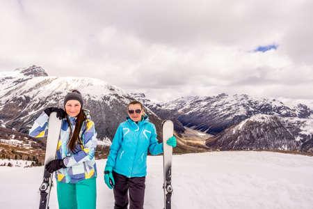 Zwei Erwachsene, glückliche und lächelnde Frau im Winterurlaub in verschneiten Bergen, Skifahrer mit Skiausrüstung, Livigno, Italien, Alpen Standard-Bild