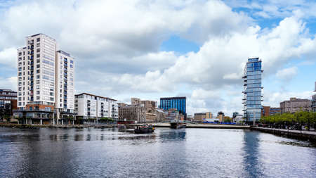 Cityscape of Dublin Docklands and river Liffey with modern buildings and barge on river. Republic of Ireland