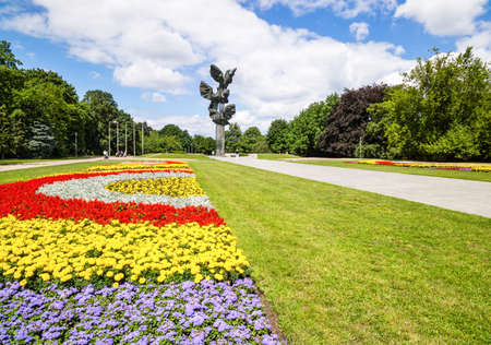 Szczecin, Poland, June 2016 Monument of Deed of Poles in the form of Three Eagles at a Kasprowicz Park with rows of colourful flowers Redactioneel