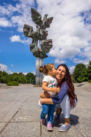 Szczecin, Poland, June 2016 Young girl kissing her mom in the chick in front of Monument of Deed of Poles at Kasprowicz Park. Happy and loving family