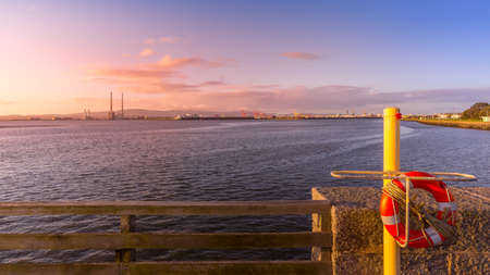 View on Dublin port with Poolbeg Power Plant, tall chimneys and dock cranes from Bull Island. Lifebuoy in first plane. Amazing sunrise, Ireland