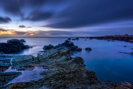 Twilight begins yielding to daylight at rocky coastline with blurred water and sky, long exposure photography. Northern Ireland