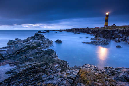 Twilight begins yielding to daylight at St. Johns Point Lighthouse. Rocky coastline with blurred water and sky, long exposure photography Reklamní fotografie