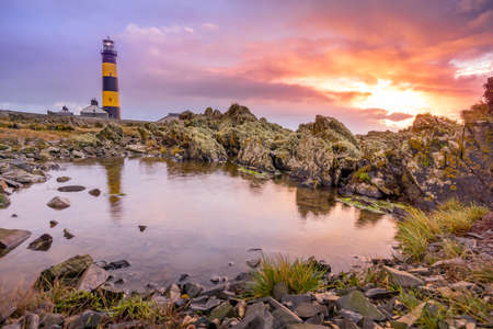 Amazing sunrise at St. Johns Point Lighthouse in County Down, Northern Ireland. Rocks reflected on small pond on coastline.