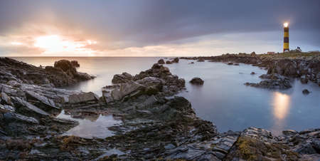 Twilight begins yielding to daylight at St. Johns Point Lighthouse. Rocky coastline with blurred water and sky, long exposure photography