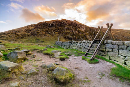 Mourn Wall with ladder on the Hares Gap overseeing Slieve Bearnagh mountain with sunset at golden hour. Mourne Mountains range in Northern Ireland Stock Photo