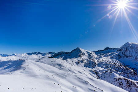 Beautiful mountain range covered in snow with clear sky, lens flare and sun star. Ski infrastructure and slopes in Pyrenees, Andorra