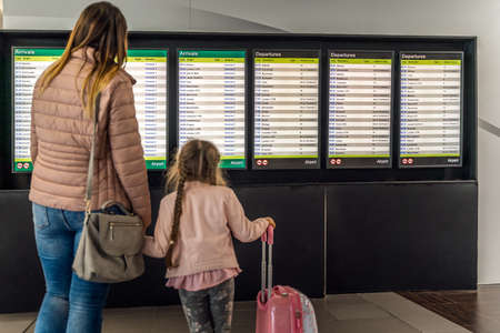Defocused silhouette of family, young girl and her mother on airport terminal. Checking arrival and departure board for their flight. Dublin, Ireland