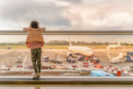 Silhouette of young girl on airport terminal. Standing on windowsill and looking on airplanes, waiting for departure. Dublin, Ireland