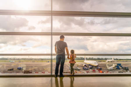 Silhouette of young family, father and daughter on airport terminal. Holding hands and looking at airplanes, waiting for departure. Dublin, Ireland 版權商用圖片
