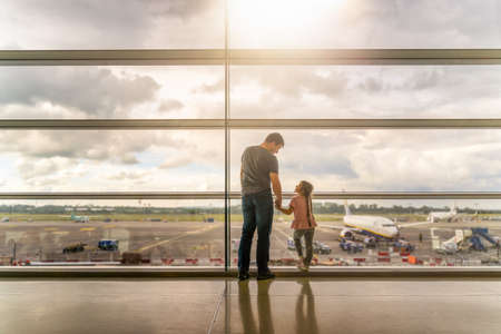 Silhouette of family, father and daughter on airport terminal. Holding hands and looking at each other, waiting for departure. Dublin, Ireland 版權商用圖片