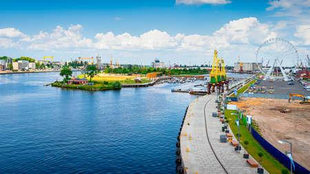 Cranes called Dzwigozaury, amusement park at Odra River Boulevards and Grodzka island with new marina, wooden bridge and motorboats, Szczecin, Poland Stok Fotoğraf