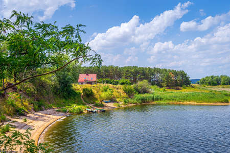 Small wield beach with few boats on an Oder River lagoon or lake with house and forest in a background, Poland. Tranquil summer scene, relaxation