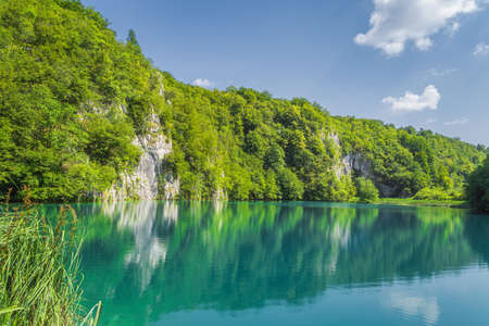 Panoramic view with tall cliff covered in trees and turquoise lake underneath it. Plitvice Lakes National Park, Croatia Zdjęcie Seryjne