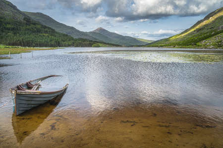 Sunken or half submerged paddle boat in Lough Gummeenduff with view on beautiful Black Valley, MacGillycuddys Reeks mountains, Ring of Kerry, Ireland