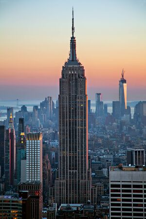 empire state building: The Empire State Building silhouette among other skyscrapers of the Manhattan skyline on the background of the Hudson Bay at sunset under clear sky; in New York City, United States of America