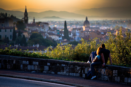 A couple in love - girl and boy sitting on a small wall by the road watching a scenic sunset over a romantic Italian city on the hills in the blurred background; in Florence, Italy Stock Photo