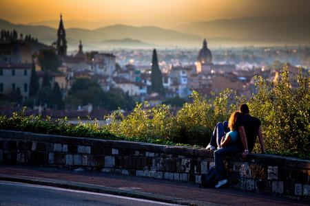 parejas romanticas: Una pareja de enamorados - niña y un niño sentado en un pequeño muro en la carretera viendo una puesta de sol escénica sobre una ciudad italiana romántica en las colinas en el fondo borroso; en Florencia, Italia