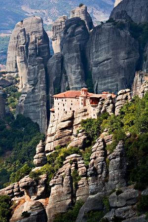 remoteness: Mountain, remote monastery on the inaccessible rocks in striking sun light on the background of hazy Greek landscape; in Meteora, Greece.