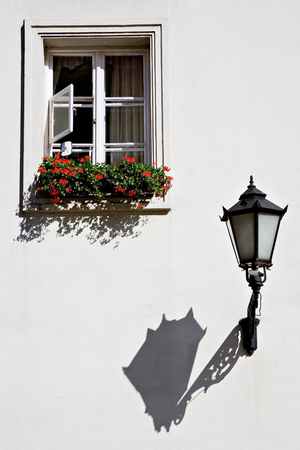 white window: An old, vintage street lamp casting a long shadow and a window decorated with red flowers on a white building wall; in Warsaw Old Town, Poland.