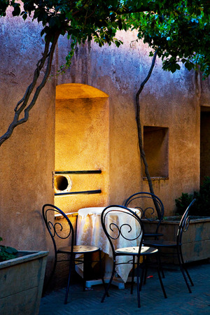 pot light: Four chairs and a table in a romantic setting under small trees, next to a window in a yellow and purple wall