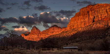 canyon walls: A setting sun shines hues of reds and pinks on the sandstone canyon walls at Zion National Park, Utah