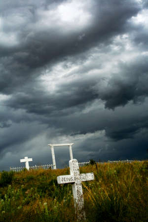 life after death: Rustic, abandoned southwesren graveyard with a dark storm in the skies