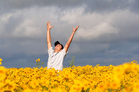 A young man stands in the midst of a field of yellow flowers, hands and arms thrown in the air in an expression of joy